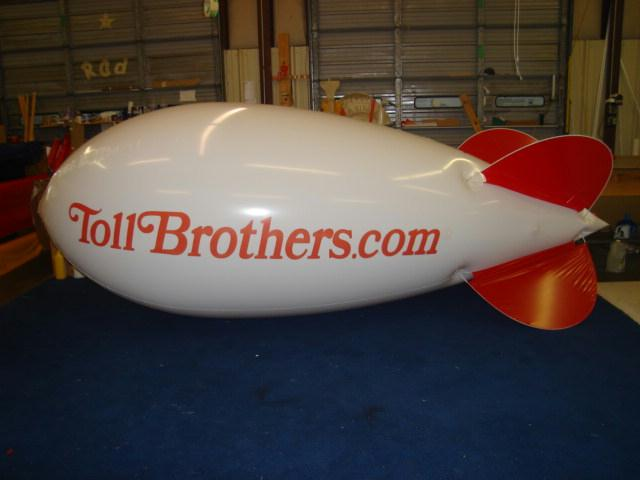 14ft long white helium blimp with TOLL BROTHERS logo